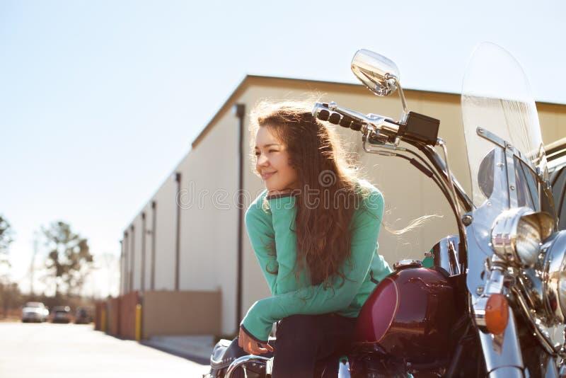 De jonge aantrekkelijke vrouw met mooie glimlach zit op rode motorfiets royalty-vrije stock fotografie