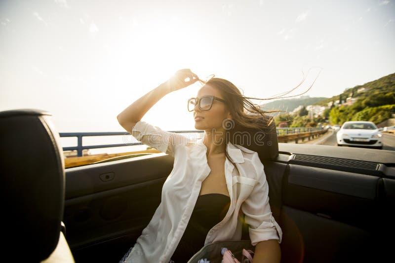 De jonge aantrekkelijke vrouw stelt in cabriolet bij kust stock afbeeldingen