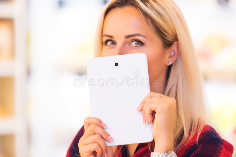 De jonge aantrekkelijke vrouw verbergt haar glimlach met een tabletcomputer stock foto