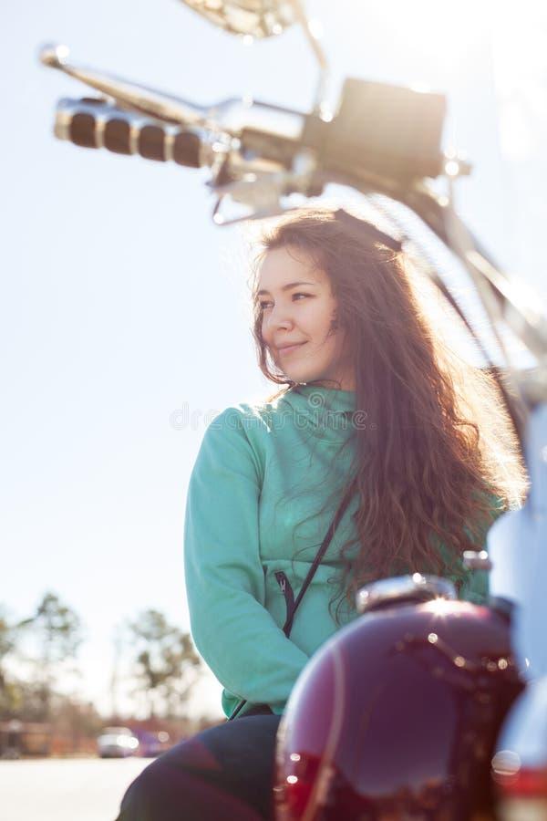 De jonge aantrekkelijke vrouw zit op rode motorfiets en kijkt opzij stock fotografie