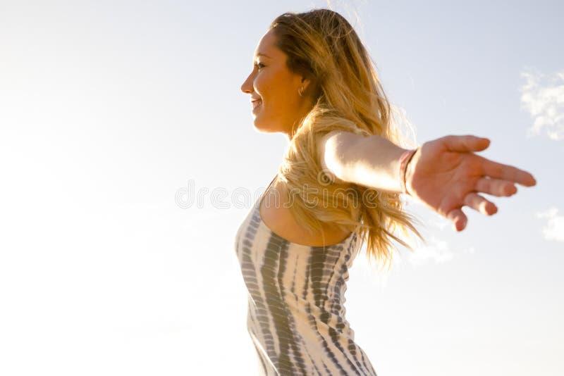 De jonge aardige vrouw geniet van haar vrijheid het openen wapens Het onafhankelijke leven en groot voelt met de wereld Omhels al stock afbeelding