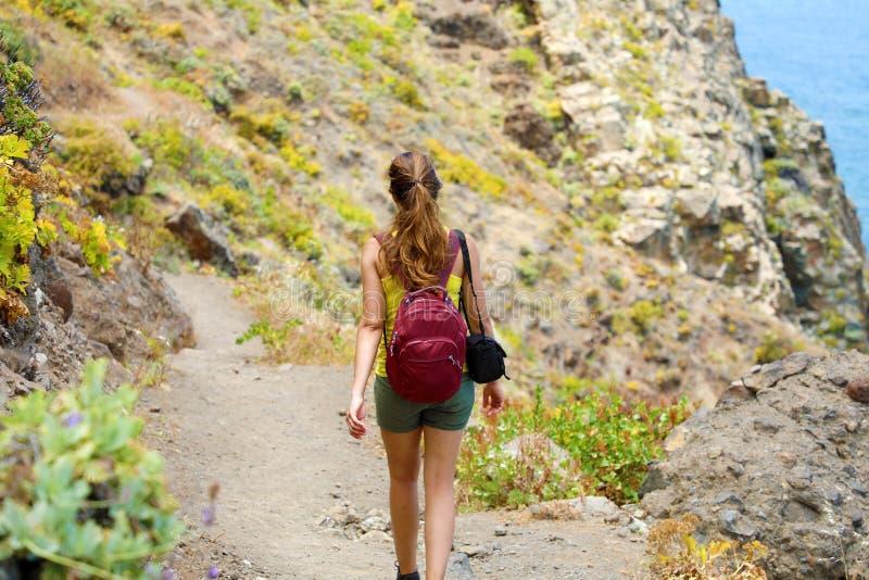 De jonge achtermening die van de wandelaarvrouw op bergweg lopen stock fotografie