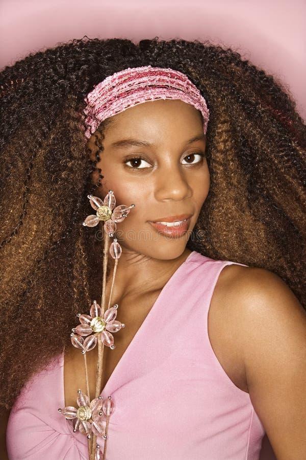 De jonge Afrikaans-Amerikaanse bloem van de vrouwenholding. royalty-vrije stock afbeelding