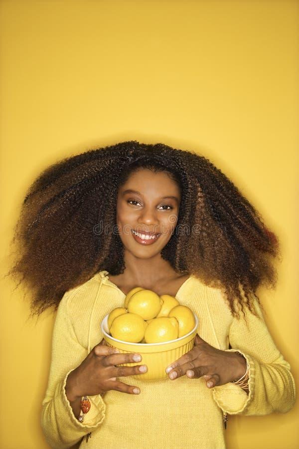 De jonge Afrikaans-Amerikaanse kom van de vrouwenholding van citroenen. royalty-vrije stock foto