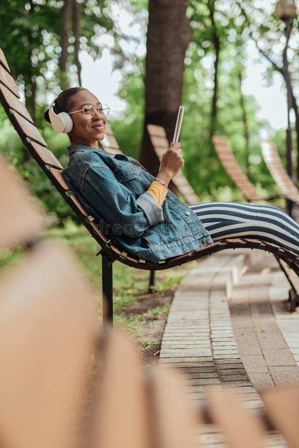 De jonge Afrikaanse Amerikaanse blocnote van de vrouwenholding in handen stock afbeeldingen