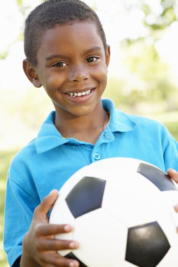 De jonge Afrikaanse Amerikaanse Voetbal van de Jongensholding in Park royalty-vrije stock fotografie
