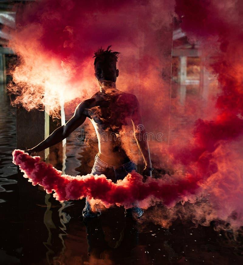 De jonge Afrikaanse mens bevindt zich onder brug en houdt gekleurde rode rookbom royalty-vrije stock foto's