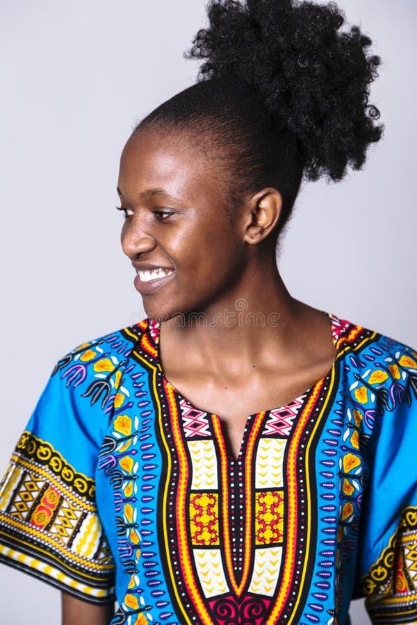 De jonge Afrikaanse vrouw in blauwe kleding kijkt zijdelings royalty-vrije stock foto