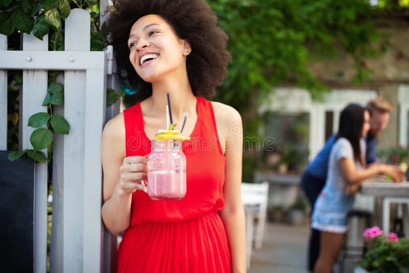 De jonge Afrikaanse vrouw geniet van gezonde vegetariër smoothie voor gewichtsverlies royalty-vrije stock fotografie