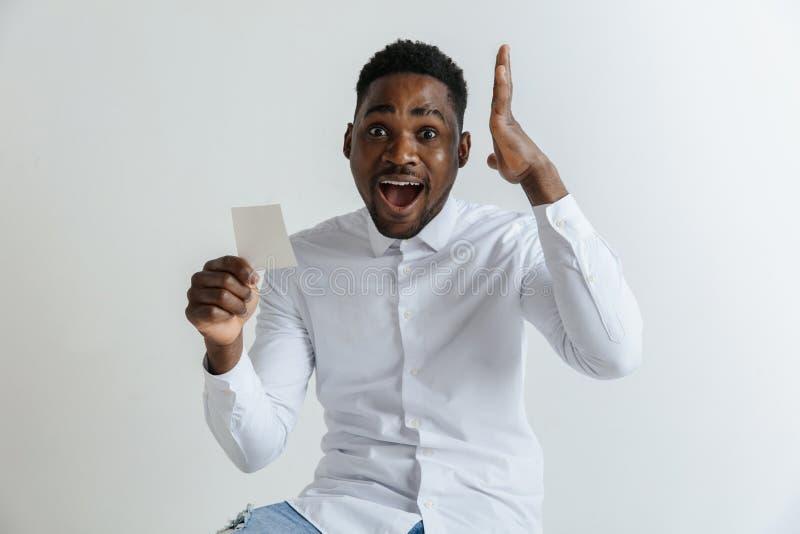 De jonge afromens met een verraste gelukkige uitdrukking won een weddenschap op grijze studioachtergrond stock foto