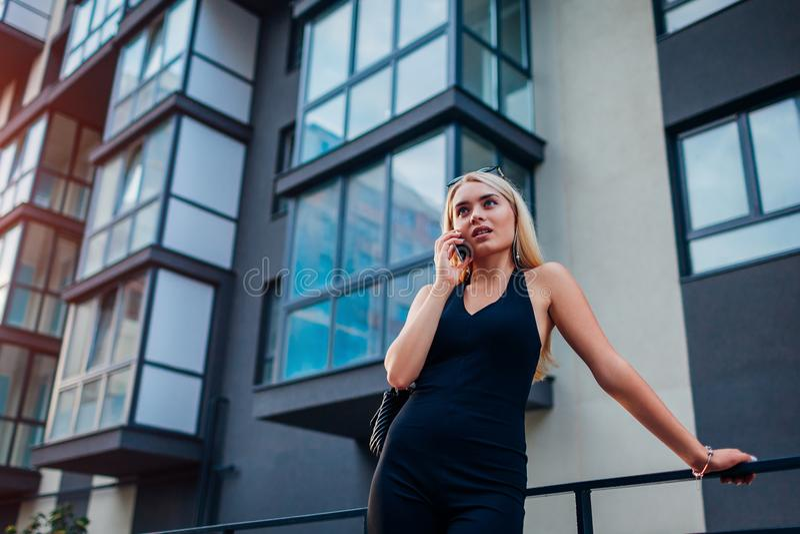 De jonge agent die van blonde echte eastate op telefoon door de moderne bouw met meerdere verdiepingen in stad spreken Onderneems royalty-vrije stock fotografie