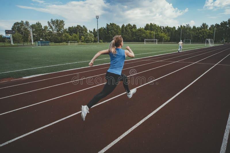De jonge agent die van de geschiktheidsvrouw op stadionspoor lopen Atletiek bij het stadion royalty-vrije stock afbeeldingen