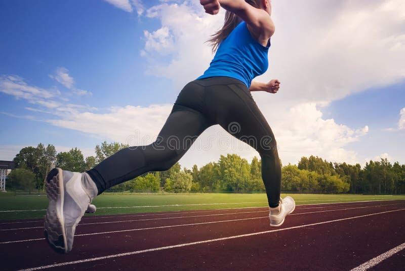 De jonge agent die van de geschiktheidsvrouw op stadionspoor lopen De tijd van de sprong tijdens de vlucht atletiek Het concept e stock afbeelding