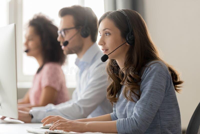 De jonge agent die van het vrouwencall centre in hoofdtelefoon online cliënt raadplegen stock afbeeldingen