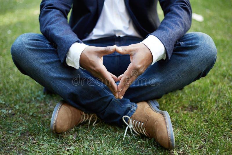 De jonge Amerikaanse Afrikaanse zakenman in formele slijtage die in lotusbloem mediteren stelt het nemen van een diepe adem buite stock foto's