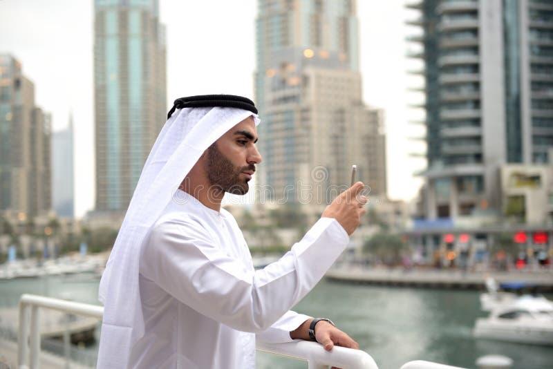 De jonge Arabische mens die van Emirati zich door het kanaal bevinden stock afbeeldingen