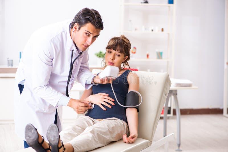 De jonge arts die de bloeddruk van de zwangere vrouw controleren royalty-vrije stock afbeeldingen