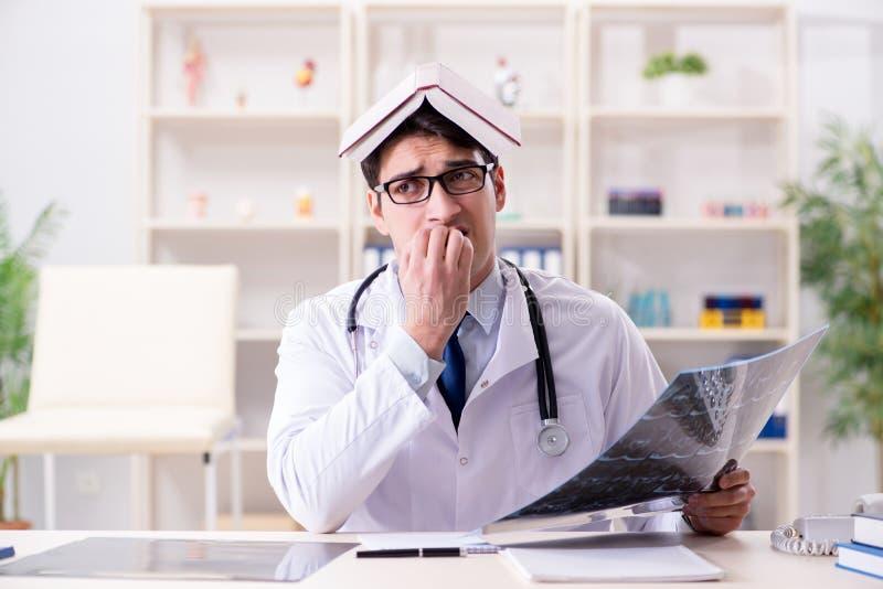 De jonge arts die x-ray beelden in kliniek bekijken stock fotografie