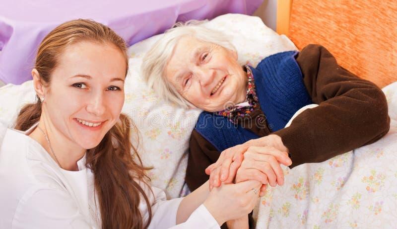 De jonge arts houdt de bejaardehanden royalty-vrije stock afbeeldingen
