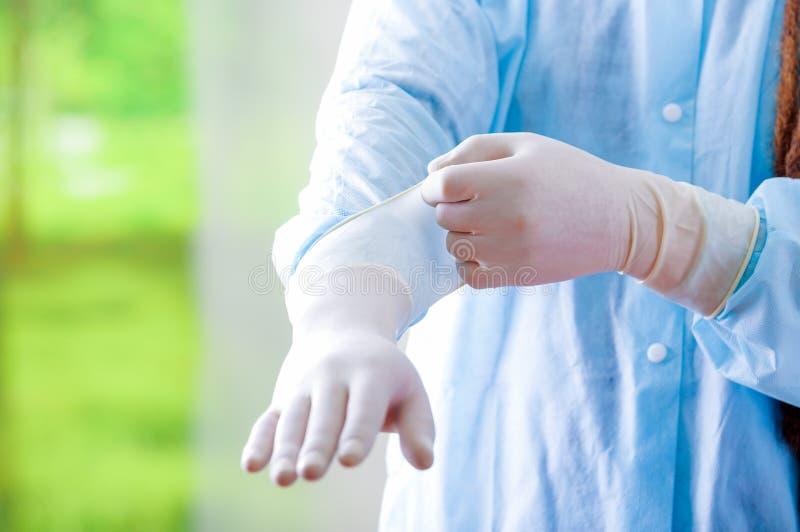 De jonge arts met lange ontzetting sluit het stellen voor camera terwijl het zetten op rubberhandschoenen, die gezichtsmasker dra stock afbeelding
