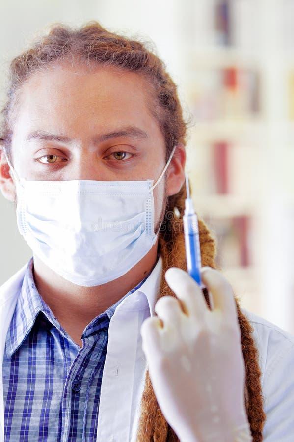 De jonge arts met lange ontzetting sluit het stellen voor de spuit van de cameraholding, die gezichtsmasker dragen die mond, klin stock afbeeldingen
