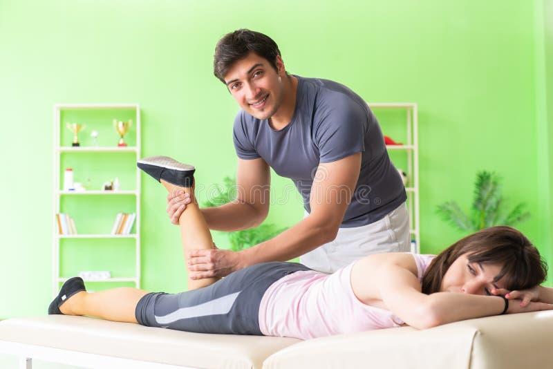 De jonge artsenchiropracticus die patiënt masseren stock foto's