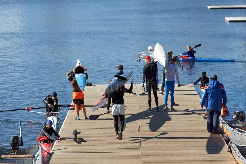 De jonge atleten treffen voor opleiding in het roeien voorbereidingen stock afbeelding