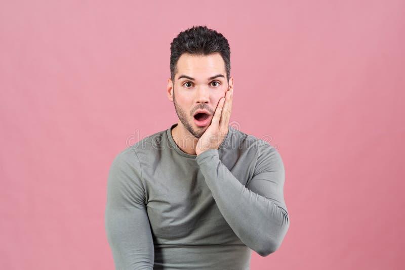De jonge atletische mens in een grijze gepaste t-shirt met een geschokte verraste uitdrukking op zijn gezicht drukt zijn hand aan royalty-vrije stock foto