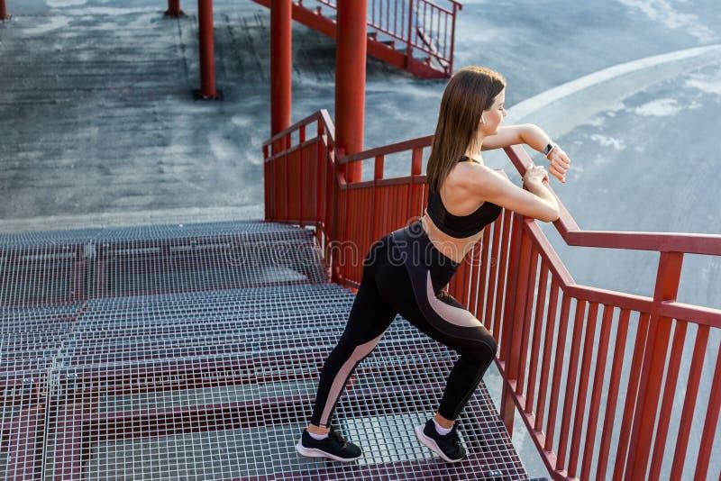 De jonge atletische slanke mooie vrouw heeft een rust en status op treden na het doen van cardiointerval opleiding in zwarte modi stock afbeelding