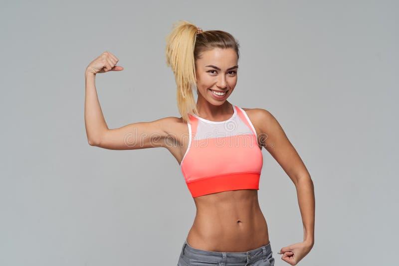De jonge atletische vrouw in een sportenbovenkant glimlacht en pronkt met haar bicepsen Atletisch bouw, washboard abs, lang blond stock foto