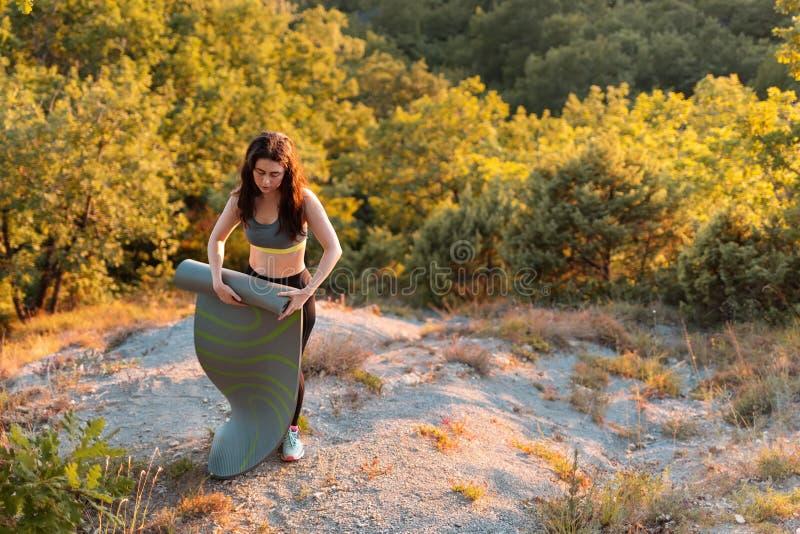 De jonge atletische vrouw na klasse verwijdert de Mat voor yoga Sporten, fitness en gezond levensstijlconcept De ruimte van het e royalty-vrije stock fotografie