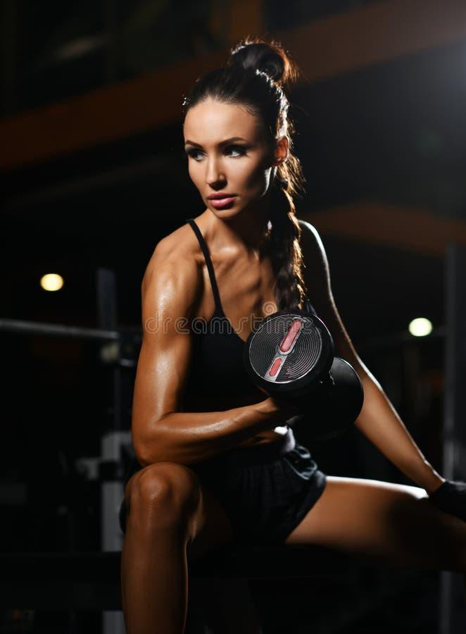 De jonge atletische vrouw werkt met domoorgewicht doend uit oefening voor wapens in gymnastiek Dieet en gewichtsverliesconcept stock afbeelding