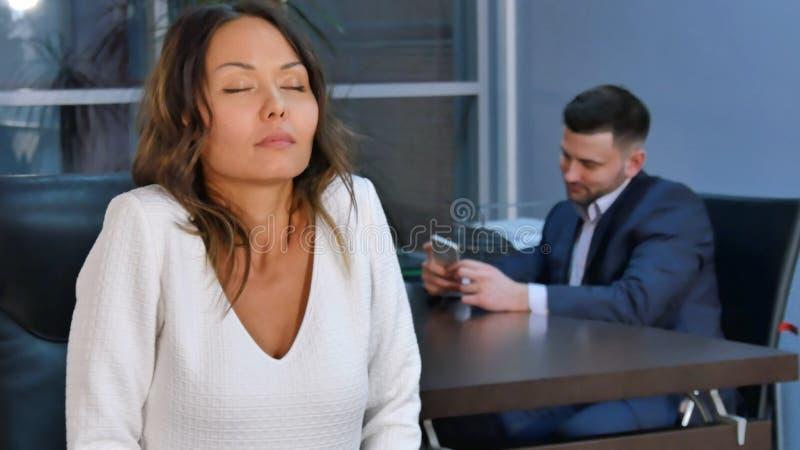 De jonge Aziatische bedrijfsvrouw ontspant na werk, die oefeningen voor handen en schouders het doen stock fotografie