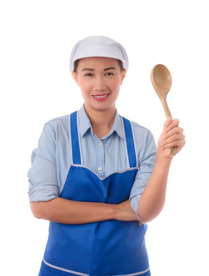 De jonge Aziatische chef-kok, zekere huisvrouw stelt en holding een spatel royalty-vrije stock afbeeldingen