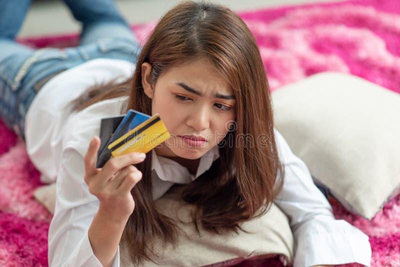 De jonge Aziatische creditcard van de vrouwenholding met beklemtoond gevoel royalty-vrije stock afbeelding