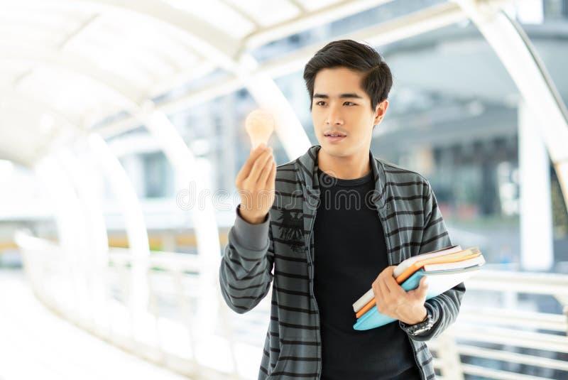De jonge Aziatische holding van de mensenstudent verlichtte gloeilamp, idee royalty-vrije stock afbeelding