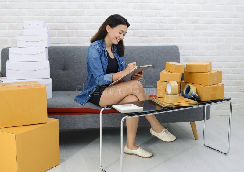 De jonge Aziatische kleine bedrijfseigenaar schrijft nota van orden van goederen met een het glimlachen gezicht royalty-vrije stock foto's