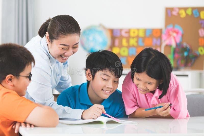 De jonge Aziatische leraar helpt jonge schooljonge geitjes in klasse royalty-vrije stock afbeeldingen