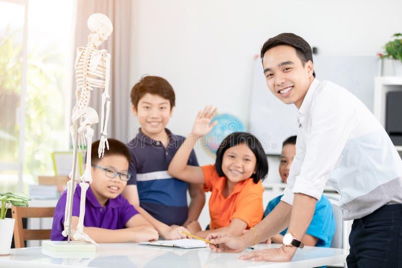 De jonge Aziatische leraar vraagt vraag jonge jonge geitjes in klaslokaal royalty-vrije stock afbeeldingen