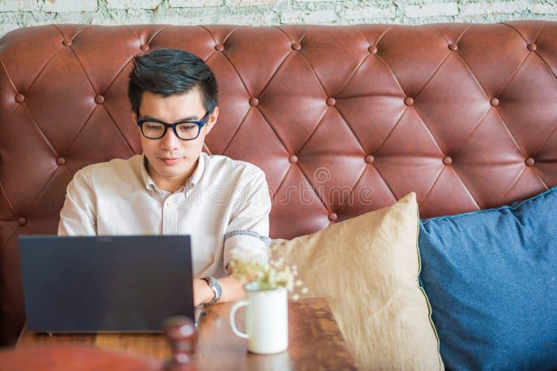 De jonge Aziatische mens het drinken koffie in koffie en het gebruiken van laptop verwerkt gegevens stock afbeeldingen