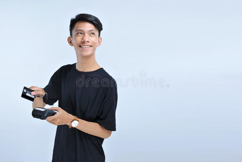 De jonge Aziatische mens jat een creditcard/een debetkaart en het bekijken de exemplaarruimte royalty-vrije stock fotografie
