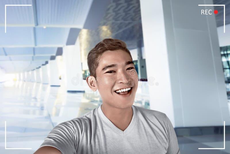 De jonge Aziatische mens stelt en neemt selfie in luchthavenhal royalty-vrije stock afbeelding
