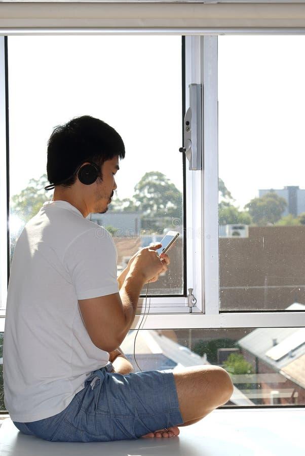 De jonge Aziatische mens zit door venster luisterend aan muziek stock afbeelding