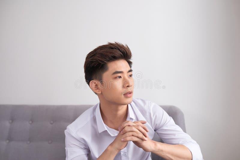 De jonge Aziatische mensenzitting op laag en de blikken dachten iets, geïsoleerd op wit royalty-vrije stock afbeelding