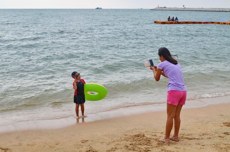 De jonge Aziatische moeder neemt een foto van haar dochter bij de oceaan royalty-vrije stock afbeeldingen