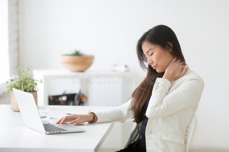 De jonge Aziatische onderneemster voelt halspijn na sedentaire comput stock afbeelding