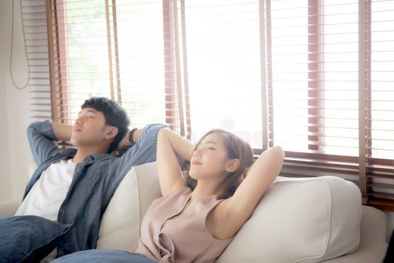 De jonge Aziatische paarglimlach ontspant comfortabel op bank in de woonkamer in vakantie, familievrije tijd en het rusten met ge royalty-vrije stock afbeelding