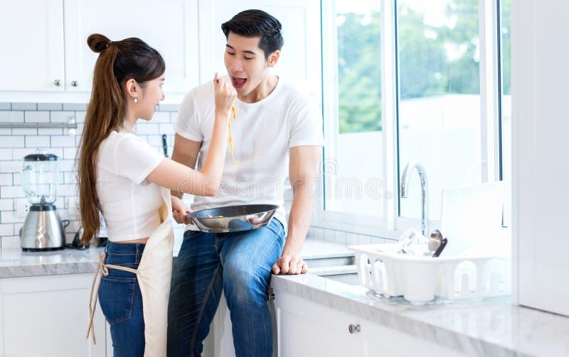 De jonge Aziatische pan van de meisjesholding met de voeder van de spaghettilepel aan jonge mensenpaar stock afbeelding