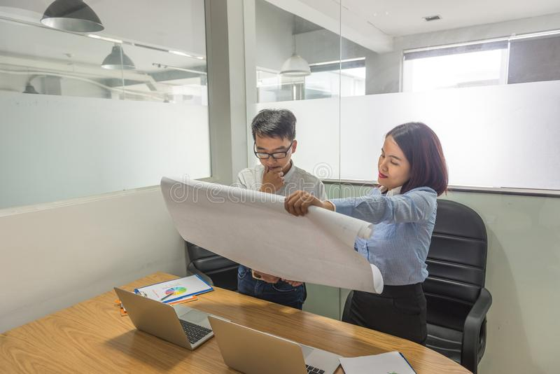 De jonge Aziatische rapporten van de managerlezing van werknemers stock foto's