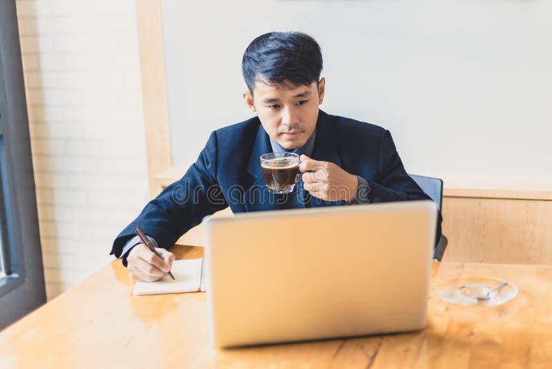 De jonge Aziatische uitvoerende zakenman geniet van drinkend zijn koffie whil stock afbeeldingen